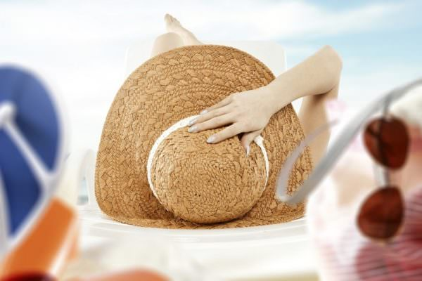 woman laying on beach with sunscreen and beach hat