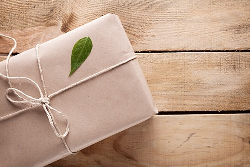 gift box with a green leaf on it on wooden background