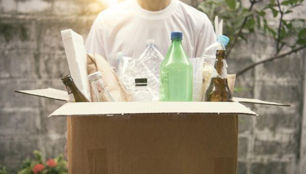 man holding cardboard box with items to recycle