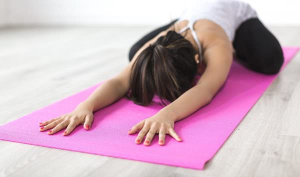 woman doing child pose on yoga mat