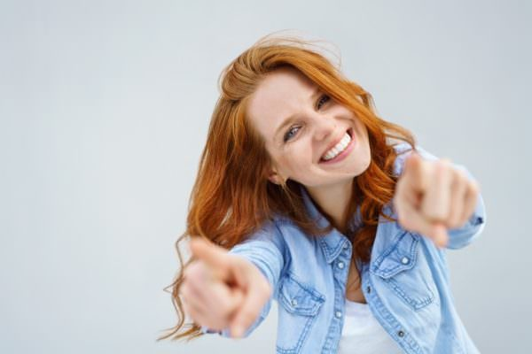 smiling young woman pointing towards viewer