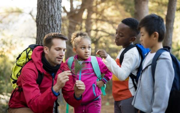 teacher and kids in woods examining plant