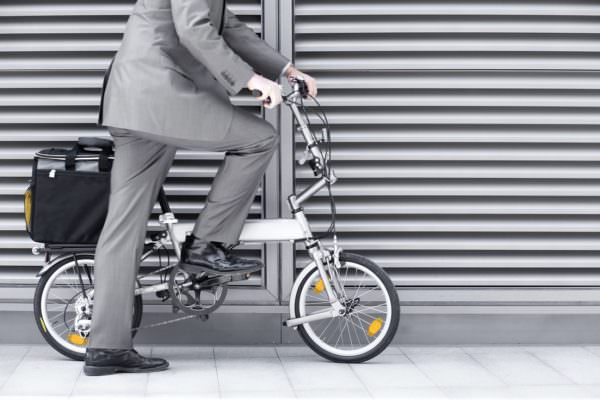 man in suit with briefcase and folding commuter bicycle