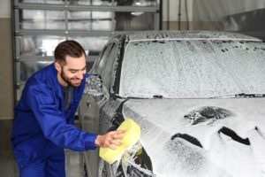 worker cleaning car with soapy sponge at car wash