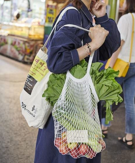 woman shopping with reusable cloth and string bags
