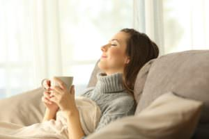 woman relaxing on sofa with a mug in her hand