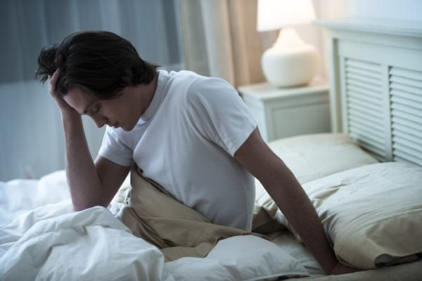 man suffering heading in bed