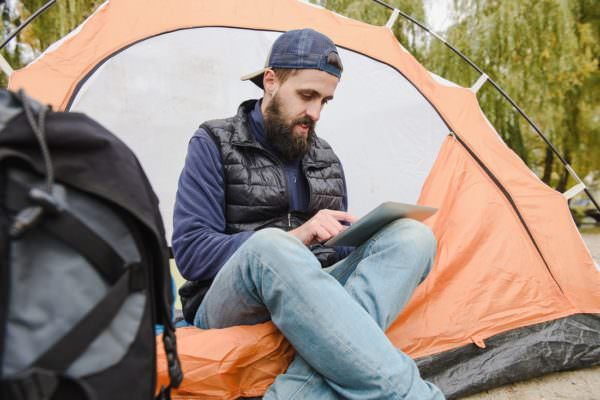 young man using iPad at camp site