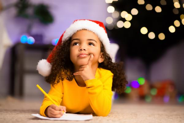 little girl writing letter to Santa by Christmas tree