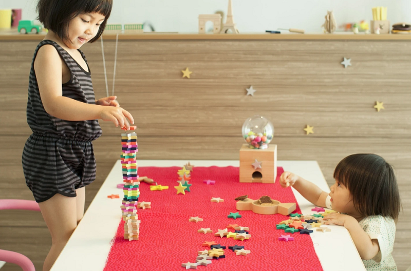 Two young girls playing with wooden star dominos