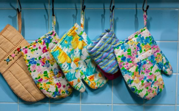 Oven mitts and potholders hanging in a row